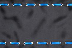 Blue satin ribbon inserted in the gold rings on black silk - stock photo