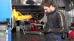 Mechanic worker man grind rusty bolts with electric grinder tool near lifted car Stock Footage