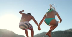 Couple Cliff Jumping Into Lake At Sunset Stock Footage