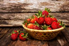 Many fresh strawberries on a wooden background. Useful treat Stock Photos