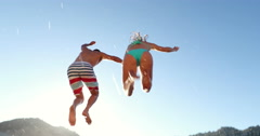 Low Angle Couple Holding Hands Jumping Into Lake In Evening - stock footage