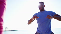 Multi Ethnic male and female by Lake Michigan sun flare stretching for exercise Stock Footage
