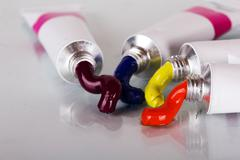Open tubes with coloured paint coming out Stock Photos