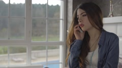 Young upset woman speaks on phone in bedroom Stock Footage