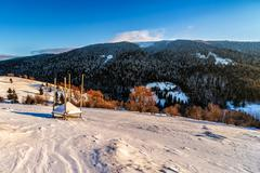 woodshed on the hillside in winter mountains - stock photo