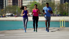Multi Ethnic male and females in Chicago city outdoors running for weightloss Stock Footage