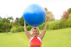 Happy senior woman with stability ball over head - stock photo