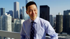 Asian American business manager on rooftop overlooking cityscape Chicago Stock Footage