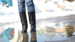 Young woman in rain boots jumping on a puddle Stock Footage