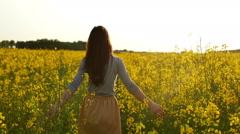 Girl walks through field, straightens hair slow mo Stock Footage