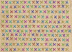 Close up of colorful cross stitch detail on designer cushion - stock photo