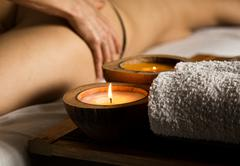 Young woman receiving a cellulite massage in the spa salon. close-up candle and - stock photo