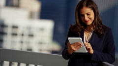 Hispanic female advisor working hot spot on city rooftop using tablet technology Stock Footage