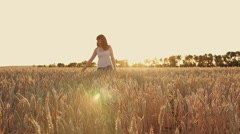 Beautiful young girl walking on a field of wheat at sunset. - stock footage