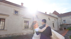 Enamoured groom takes the bride in his arms and twirl her round in the streets Stock Footage