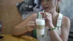 Girl brunette drinking coffee latte through a straw Stock Footage