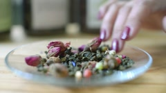 Tea leaves and flowers poured on a saucer - the art of beautiful tea Stock Footage
