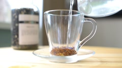 In a cup of tea leaves is poured boiling water Stock Footage