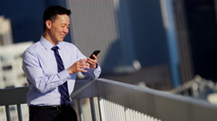 Male Asian Chinese manager working hot spot on rooftop using mobile technology Stock Footage