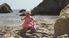 The happy little girl on the seashore plays with pebble - stock footage