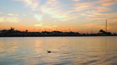 Sunrise over the ocean casting orange and blue sky and clouds during the summer Stock Footage
