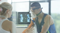 4K Man with breathing equipment on exercise bike having fitness levels analyzed Stock Footage