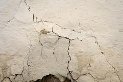 Craked white painted wall with large fissures on the mottled shaded plaster s Stock Photos