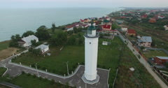 Sea lighthouse on the coast in the summer during sunset Stock Footage