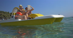 Family in pedal boat taking selfie with pad Stock Footage