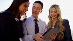 Portrait of multi ethnic business advisors using tablet technology on rooftop Stock Footage