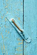 Single old metal door handle on faded aged light blue paint. Copy space area  Stock Photos