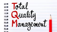 TQM Total Quality Management written on notebook page - stock photo