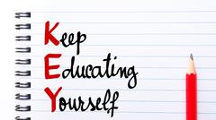 KEY Keep Educating Yourself written on notebook page - stock photo