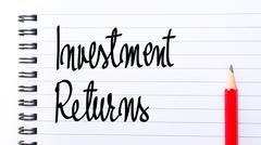 Investment Returns written on notebook page - stock photo