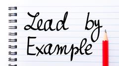 Lead By Example written on notebook page Stock Photos