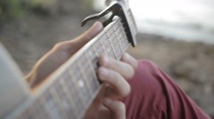 A man plays the guitar while sitting by the sea. Close up Stock Footage