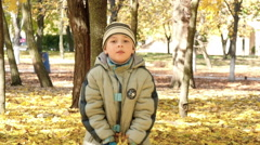 boy throws fallen leaves in autumn park, slow motion 2 - stock footage