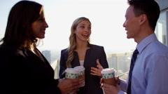 Young multi ethnic business managers enjoying coffee on Chicago city rooftop Stock Footage