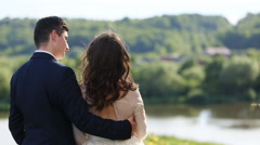 Just married couple, bride wearing wedding dress and groom with black suit, lake Stock Footage