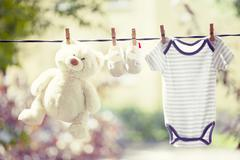 Baby clothes, boots and teddy hanging on the clothesline - stock photo