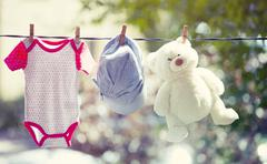 Baby clothes, hat and teddy hanging on the clothesline - stock photo