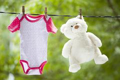 Baby clothes and teddy bear hanging on the clothesline - stock photo