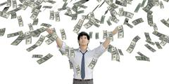 Asian Man Catching Money Falling From the Sky - stock photo