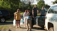 Volunteers Carry Ice to Flood Victims Stock Footage