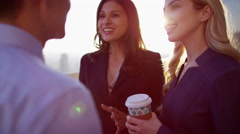 Meeting of young multi ethnic business people drinking coffee on city rooftop Stock Footage