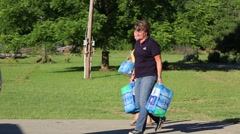 Volunteers Carrying Bottled Water for Flood Victims Stock Footage