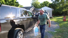 Bearded Man Places Ice in SUV for Flood Victims Stock Footage