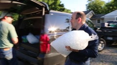 Man Passes Bag of Ice to Another to Load in SUV for Flood Victims Stock Footage