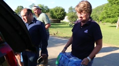 Volunteers Placing Bottled Water in SUV for Flood Victims Stock Footage