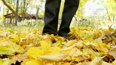 man walking on the fallen leaves in autumn park, slow motion  - stock footage